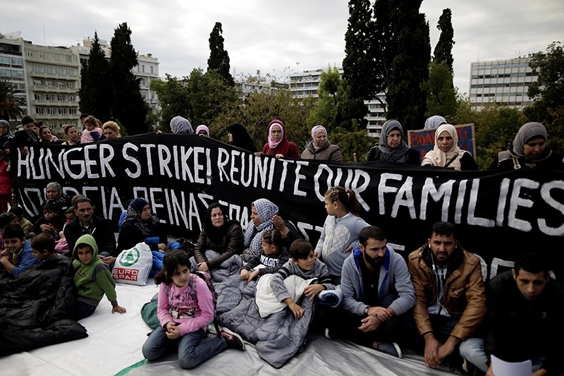 Refugees seeking reunification with family members in Germany sit in front of a banner announcing a hunger strike during a protest near the parliament building in Athens, Greece, November 1, 2017. (Reuters Photo)