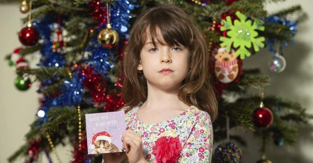 Florence Widdicombe, 6, poses with a Tesco Christmas card from the same pack as a card she found containing a message from a Chinese prisoner, in London, Sunday, Dec. 22, 2019. (AP Photo)