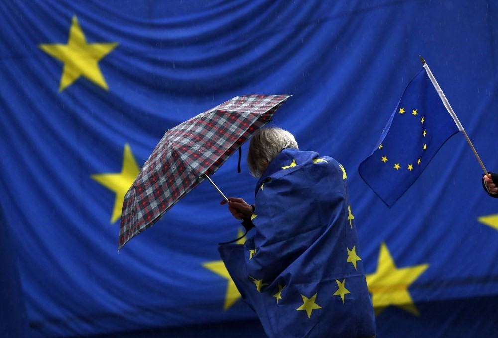 A participant wrapped in a European flag protects herself from the rain during the monthly pro-European Union rally titled, 'Pulse of Europe,' in Berlin, Germany, Nov. 25.