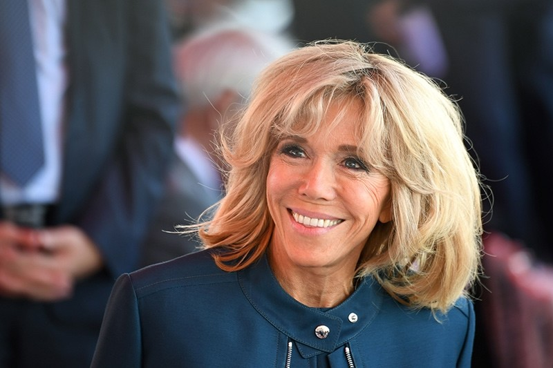 This file photo taken on July 14, 2017 shows  Brigitte Macron (C), wife of French President, smiling ahead of the start of the annual Bastille Day military parade on the Champs-Elysees avenue (AFP Photo)