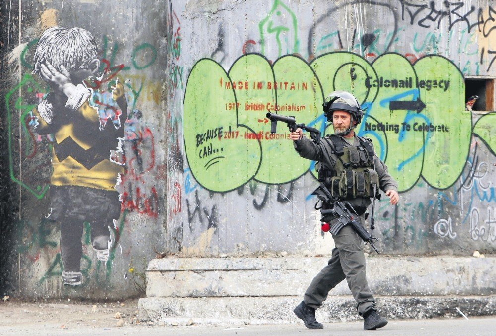 An Israeli police officer aims his weapon during clashes with Palestinian civilians, who are protesting against U.S. President Donald Trumpu2019s controversial decision to recognize Jerusalem as the capital of Israel, Bethlehem, Dec. 20, 2017.