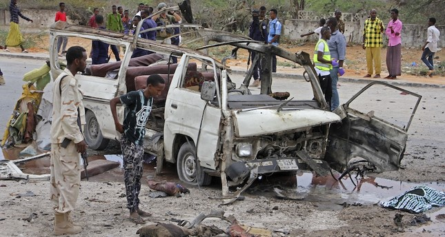 A Somali soldier, left, stands by the wreckage of a passing minibus that was destroyed in a suicide car bomb attack near the defense ministry compound in Mogadishu, Somalia Sunday, April 9, 2017. AP Photo