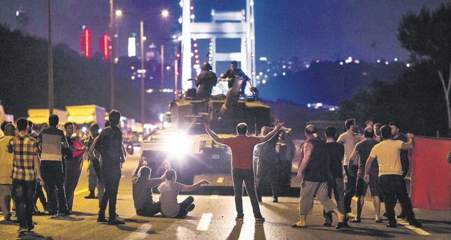 People take over a tank near the Fatih Sultan Mehmet bridge during clashes with military forces in Istanbul.