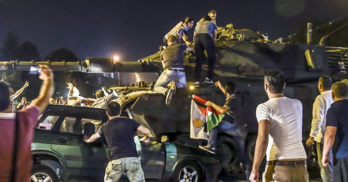 People climb over a tank controlled by putschists on July 15, 2016, to stop the coup attempt that killed 251 people and injured 2,200 others.