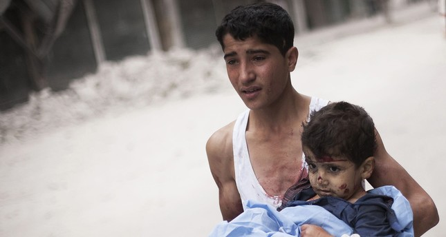 A Syrian youth holds a child wounded by Syrian Army shelling near Dar El Shifa hospital in Aleppo, Syria, Thursday, Oct. 11, 2012. (AP Photo)