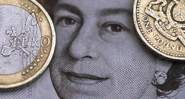 A two Euro coin is pictured next to a one Pound coin on top of a portrait of Britain's Queen Elizabeth in this file photo illustration shot March 16, 2016. (Reuters Photo)