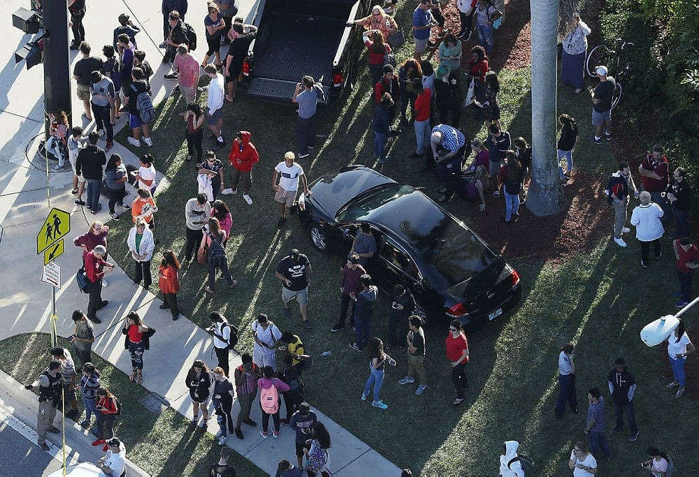 People wait for loved ones as they are brought out of the Marjory Stoneman Douglas High School after a shooting at the school that reportedly killed and injured multiple people on Feb. 14, 2018. ()