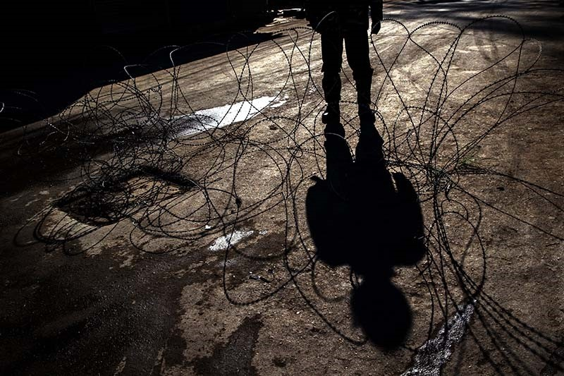 A shadow of an Indian paramilitary soldier is cast on barbed wire at a checkpoint during curfew in Srinagar, Indian controlled Kashmir (AP Photo)