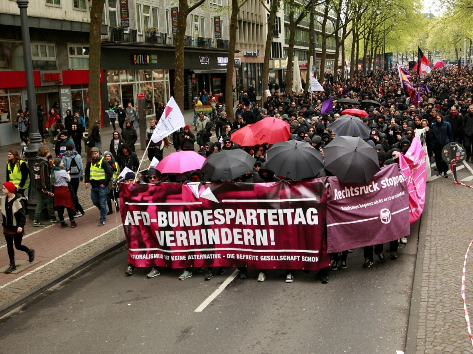 Anti-AfD protestors yield anarchist flags and banners accusing the party of racism, Cologne, April 22-23.