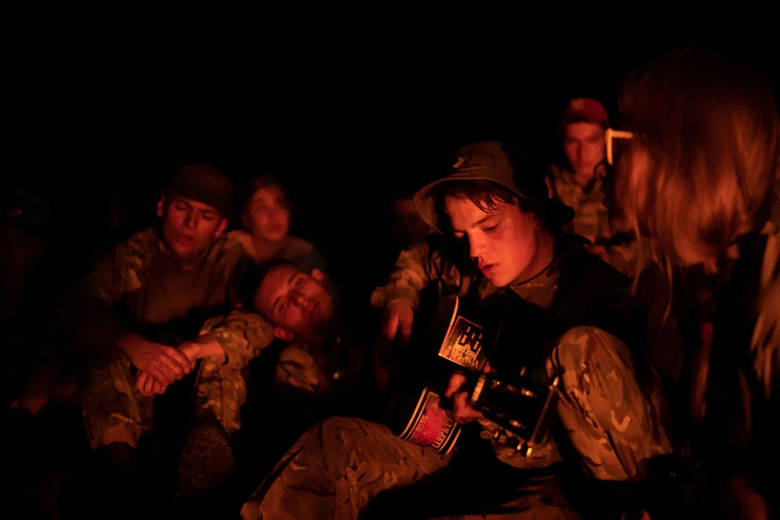A young participant of the camp plays a guitar decorated with a sticker depicting bombs hitting a mosque, as others sing around a bonfire.