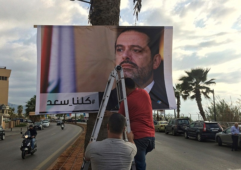 Workers hang a poster of outgoing Prime Minister Saad Hariri with Arabic words that read, ,We are all Saad,, on a seaside street in Beirut, Lebanon, Nov. 9, 2017. (AP Photo)