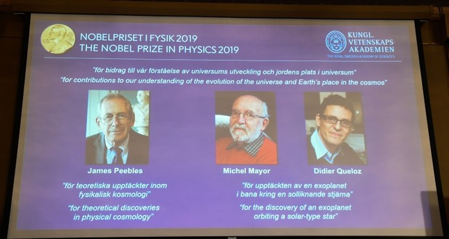 A screen displays the portraits of the laureats of the 2019 Nobel Prize in Physics (AFP Photo)