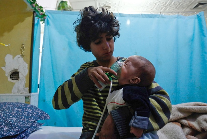 A Syrian boy holds an oxygen mask over the face of an infant at a make-shift hospital following a reported gas attack on Douma in the eastern Ghouta region near capital Damascus on January 22, 2018. (AFP Photo)
