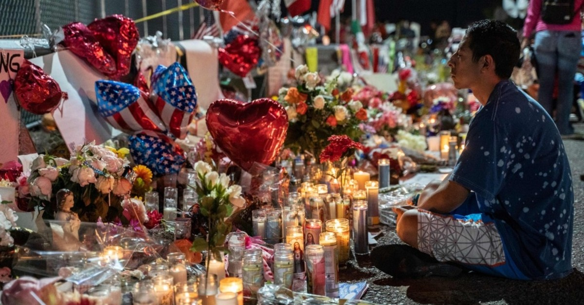 A local resident meditates in front of the makeshift memorial for shooting victims at the Cielo Vista Mall Walmart in El Paso, Texas, Aug. 8, 2019.