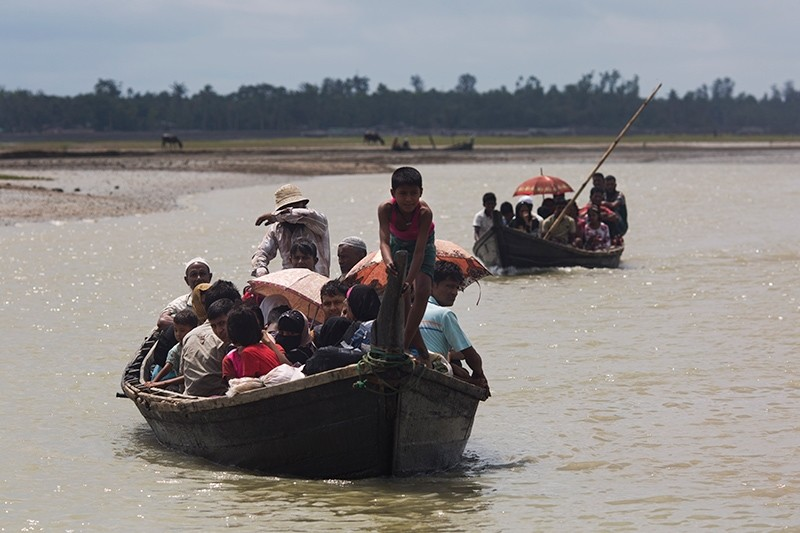 Myanmar's Rohingya Muslim minority use a local boat to cross a stream after crossing over to the Bangladesh side of the border near Cox's Bazar's Dakhinpara area, Sept. 2, 2017. (AP Photo)