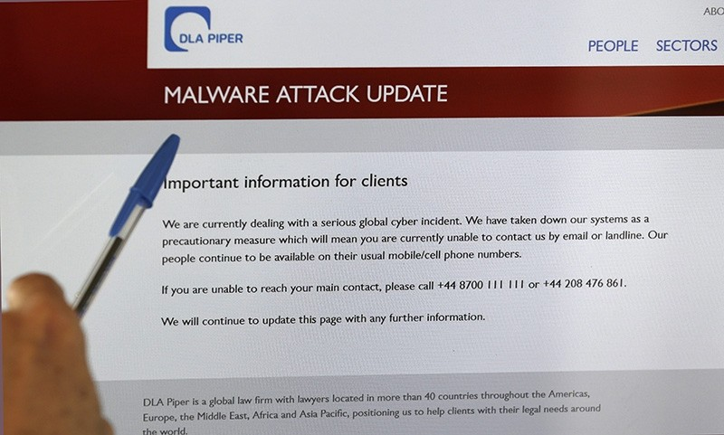 A screen displays the website of the global law firm DLA Piper showing a message about a malware attack (EPA Photo)