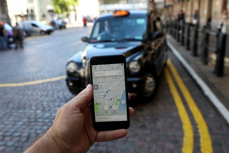 A photo illustration shows the Uber app and a black cab in London, Britain June 26, 2018. (Reuters Photo)