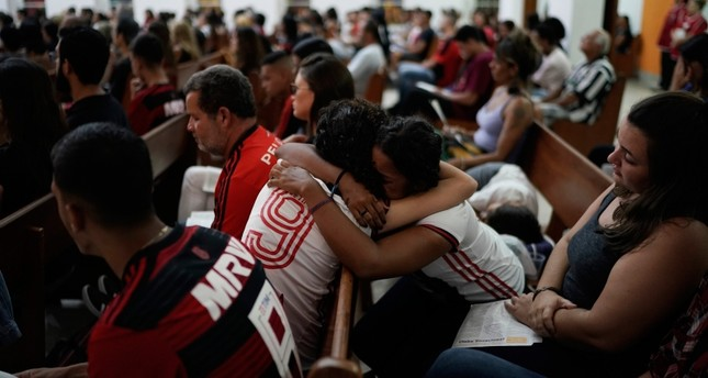Two young women, wearing Flamengo soccer kits, embrace as they attend a memorial Mass for the victims of a fire at a Brazilian soccer academy, in Rio de Janeiro, Brazil, Friday, Feb. 8, 2019. (AP Photo)