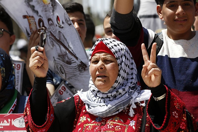 A Palestinian woman holds the key to her old family house as Palestinians carry Palestinian flags and banners as they stage a rally to mark the 69th anniversary of 'Nakba Day', in the West Bank city of Ramallah, May 15, 2017. (EPA Photo)