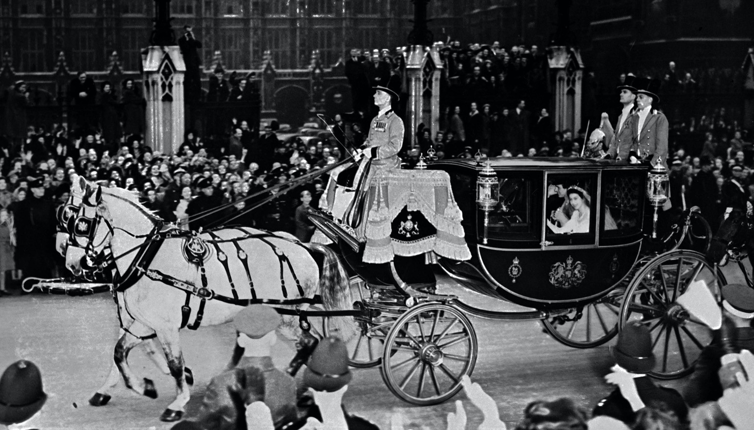 Queen Elizabeth II (in coach) and her husband Prince Philip are cheered by the crowd after their wedding ceremony in 1947.