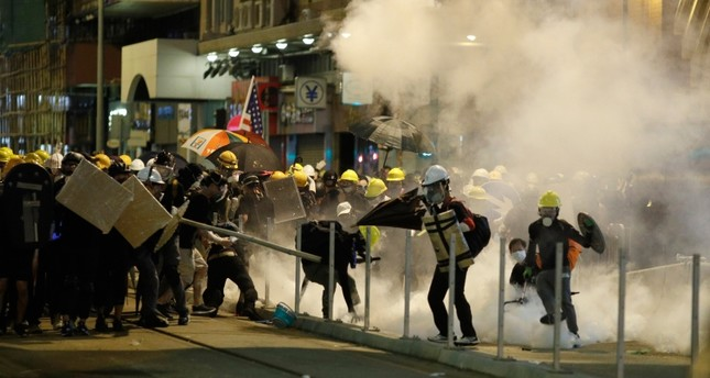 Protesters react to teargas as they confront riot police officers in Hong Kong on Sunday, July 21, 2019. (AP Photo)
