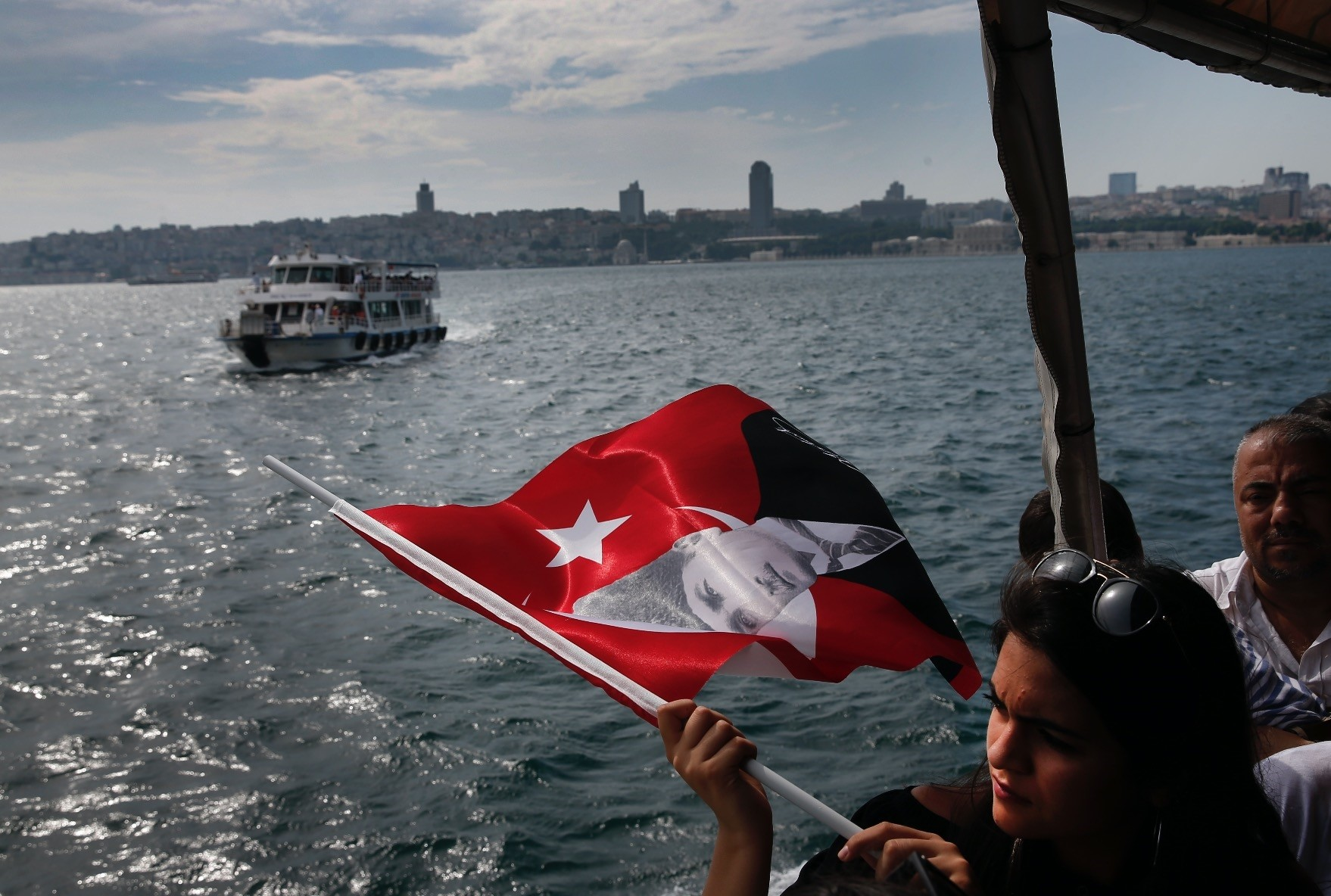 Aboard a boat crossing the Bosporus, separating Asia and Europe, a woman holds a Turkish flag decorated with a picture of Turkish Republic founder Mustafa Kemal Atatu00fcrk, Istanbul, June 16.