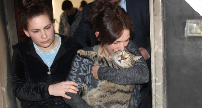 Canan Ş. hugs her cat after the fire as she sees the extent of damage in her home. (IHA Photo)