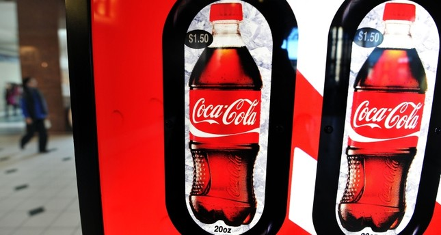In this file photo taken on February 15, 2011, a woman walks past a Coca Cola vending machine at a shopping mall in Arlington, Virgina. (AFP Photo)