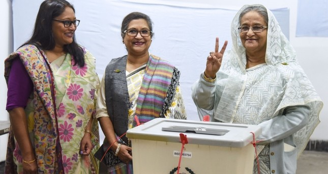 Bangladeshi Prime Minister Sheikh Hasina (R) flashes the victory symbol after casting her vote, as her daughter Saima Wazed Hossain (1st L) and her sister Sheikh Rehana (2nd L) look on at a polling station in Dhaka on December 30, 2018. (AFP Photo)