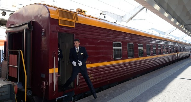 A train conductor steps down from a car of the first tourist train passing through Russia's Arctic regions to Norway as it prepares to leave Saint Petersburg for a 11-day trip with 91 passengers on board, June 5, 2019. (AFP Photo)