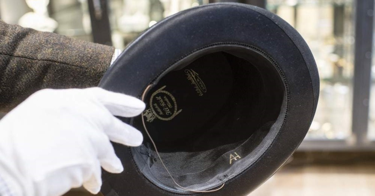 A man holds a hat with the initials of Adolf Hitler prior to an auction in Grasbrunn, Germany, Wednesday, Nov. 201, 2019. (AP Photo)