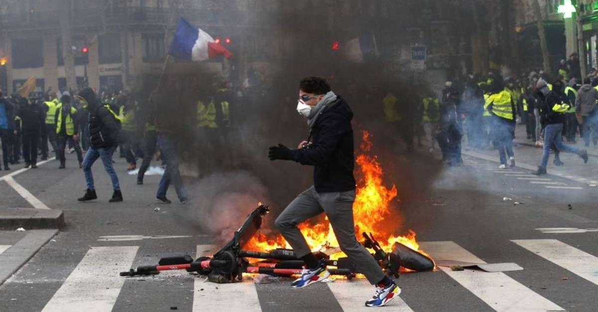 A demonstrator runs by a fire during a yellow vest protest, Paris, Feb. 2, 2019. (AP Photo)