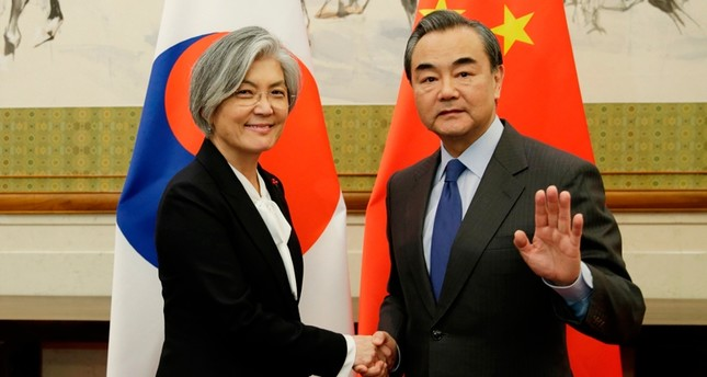 China's Foreign Minister Wang Yi (R) shakes hands with South Korea's Foreign Minister Kang Kyung-wha at the Diaoyutai State Guesthouse in Beijing ( AFP Photo)