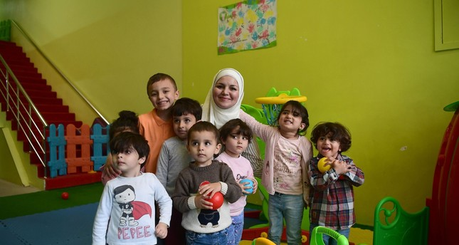 Creche owner Dania Abdulbaqi (C) poses with children in Gaziantep. Opposition leaders, especially presidential candidates Muharrem İnce and Meral Akşener, have been openly hostile to Syrian refugees.