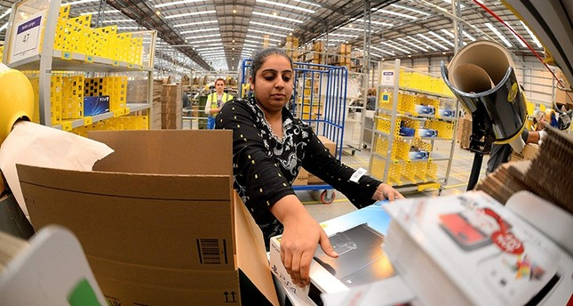 This file photo taken on Nov. 28, 2013, shows an employee packing orders at the Fulfillment Center for online retail giant Amazon in Peterborough, central England. (AFP Photo)