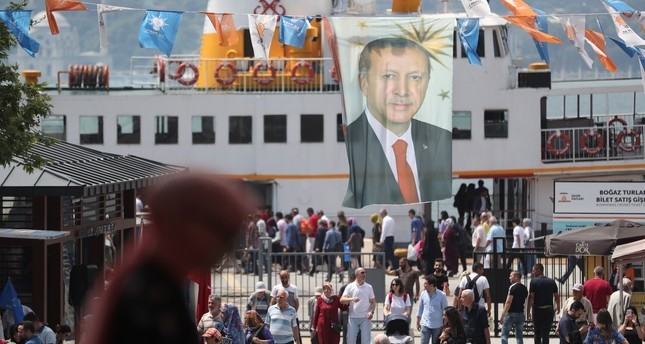 People walk under a huge picture of Turkish President Recep Tayyip Erdoğan in Istanbul weeks before the elections on June 24. The Turkish growing economy is expected to continue to expand in the coming years under Erdoğan's stewardship.