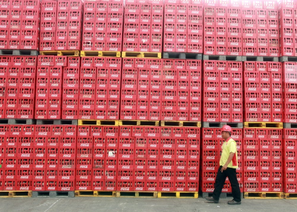 An Indonesian worker walks past crates at the Coca Cola Amatil plant in Cibitung, Indonesia.