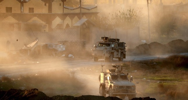 U.S. Army vehicles backing the forces of the SDF, the YPG-affiliated nonstate Syrian group, drive through Hajin, in Deir ez-Zor province, Syria, Dec. 15, 2018.