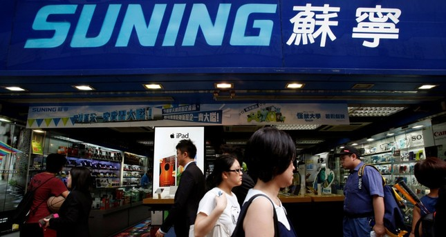 People walk past a Suning store, one of the largest home appliance retailers in Hong Kong.