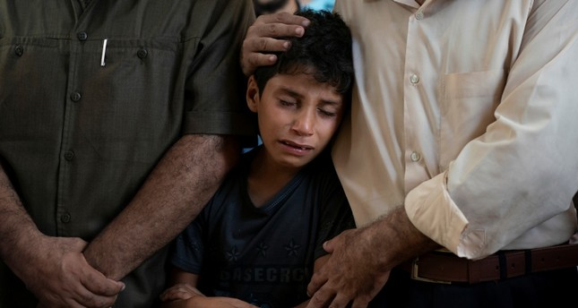 Mahmoud Abdel-al, 11, cries during the funeral of his twin brother Shady