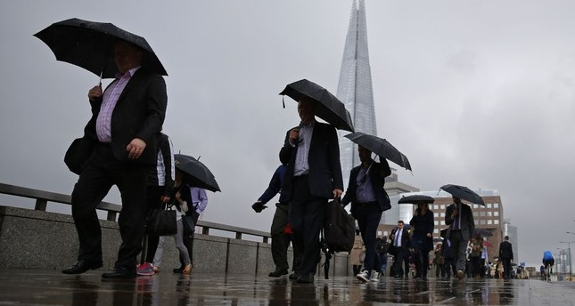 Commuters heading into the City of London walk in the rain across London Bridge in front of the Shard skyscraper in central London yesterday. Britain's Treasury chief yesterday sought to ease concerns about Brexit.