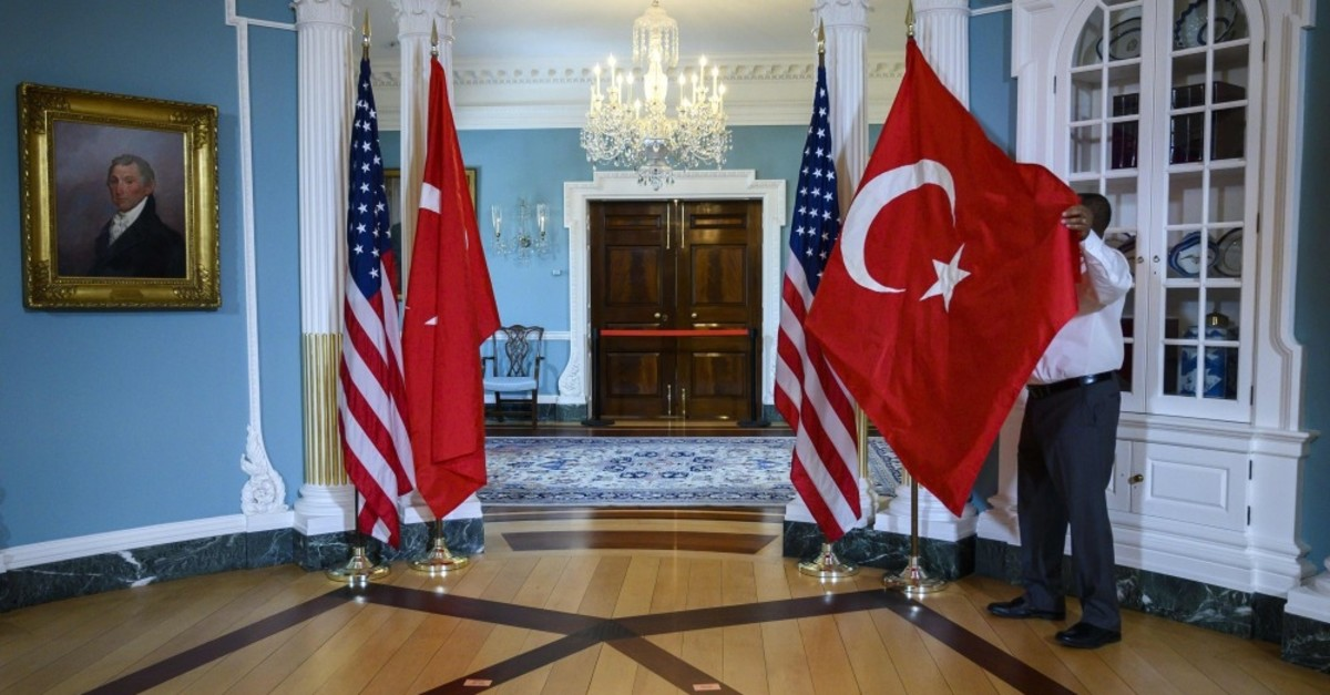 A U.S. State Department staffer adjusts a Turkish flag before a meeting between Foreign Minister Mevlu00fct u00c7avuu015fou011flu and U.S. Secretary of State Mike Pompeo at the State Department in Washington, D.C., April 3, 2019.