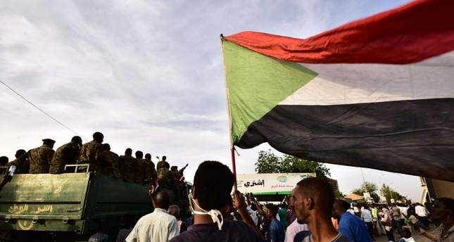 Sudanese demonstrators gather as an army vehicle drives by, near the military headquarters in the capital Khartoum on April 14, 2019. (AFP Photo)