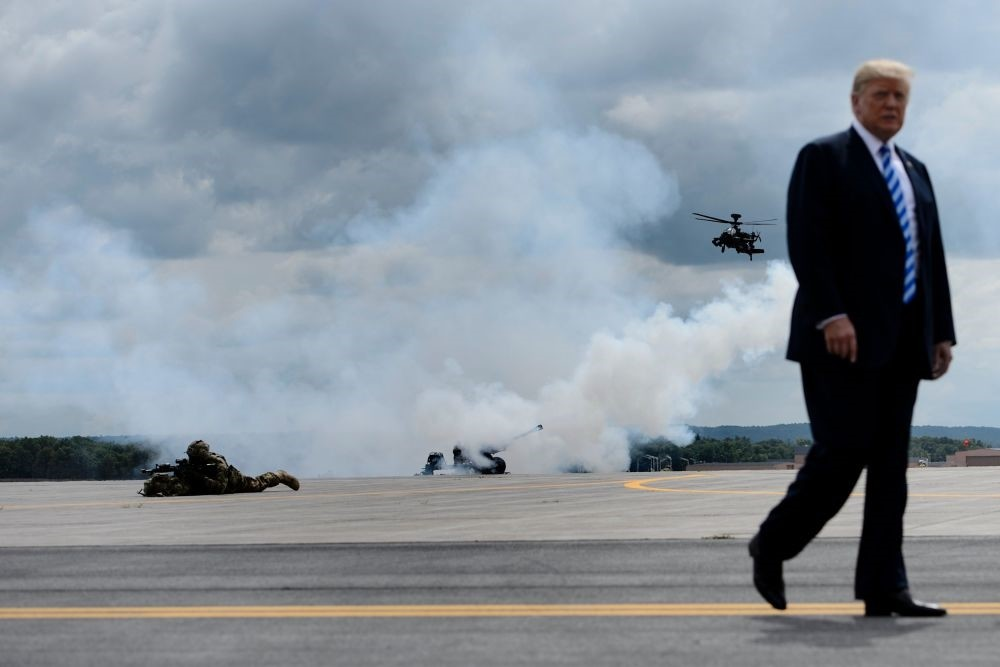 U.S. President Donald Trump walks as a canon fires in the background during an air assault exercise at Fort Drum Aug. 13, 2018 in New York.