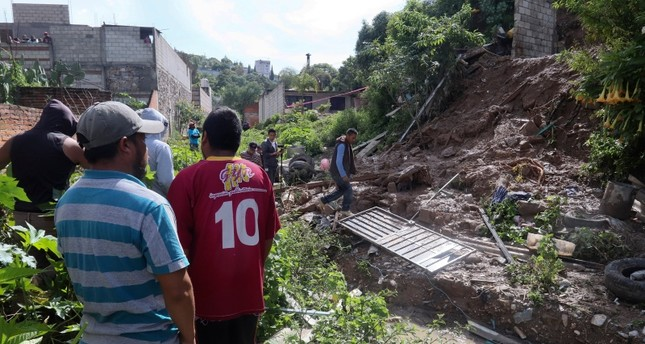 People walk at the scene of a deadly mudslide in Santo Tomas Chautla, Mexico, Thursday, July 11, 2019. AP Photo