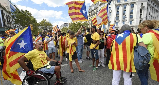 People wave 'Esteladas' (pro-independence Catalan flags) as they gather before a pro-independence demonstration, on September 11, 2017 in Barcelona during the National Day of Catalonia, the Diada. (AFP Photo)