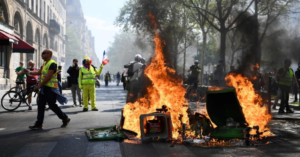 Protesters stand next to a burning barricade during an anti-government demonstration called by the ,Yellow Vests, (gilets jaunes) movement, on April 20, 2019 in Paris (AFP Photo)