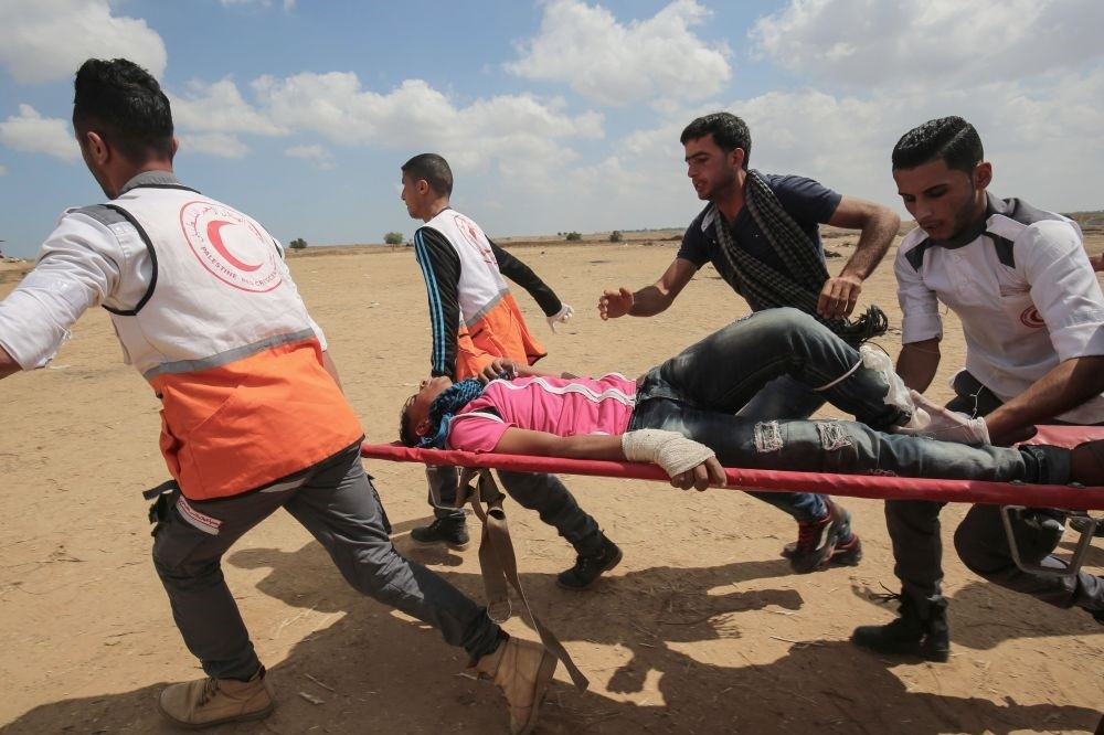Palestinians carry a protester injured by Israeli forces along the border with the Gaza Strip east of Khan Yunis on May 14.