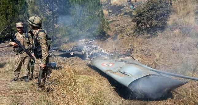 Pakistani soldiers stand next to the wreckage of an Indian fighter jet shot down in Pakistan-controlled Kashmir at Somani area in Bhimbar district near the Line of Control on Feb. 27, 2019. Photo by STR / AFP