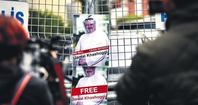 Pictures of slain Saudi journalist Jamal Khashoggi are seen on a fence set up by police in front of the Saudi Consulate in Istanbul during a demonstration, Oct. 14, 2018.